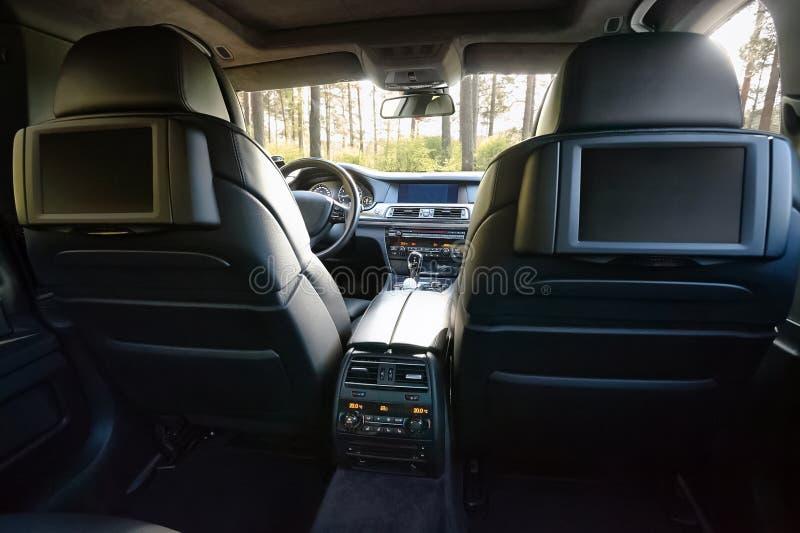 Automobile all'interno Interno dell'automobile moderna di lusso di prestigio Tre esposizioni della TV per il passeggero con lo sp fotografia stock