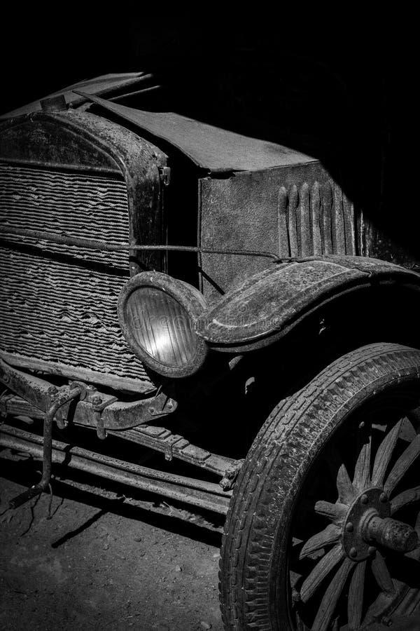 Automobile antica in bianco e nero con la griglia, la gomma ed il faro anteriori visibile fotografia stock