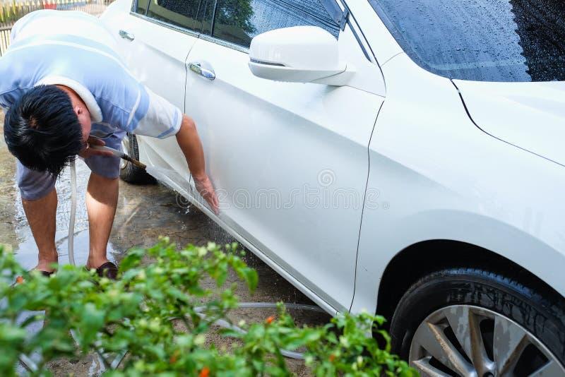 Automobile asiatica di lavaggio del giovane vicino al giardino domestico all'aperto con il tubo flessibile a immagini stock libere da diritti