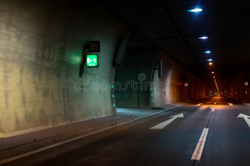 Automobile auto dark car tunnel with white arrows on asphalt showing way direction. Emergency exit sign with many lights royalty free stock photos