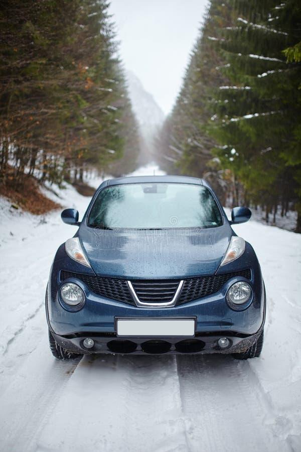 Automobile blu sulla strada nevosa, orario invernale immagini stock