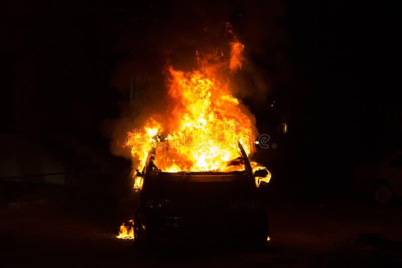 Automobile bruciante sulla strada nella notte fotografia stock