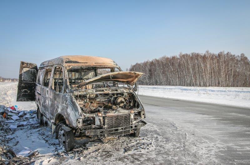 Automobile bruciata sola su una strada principale suburbana immagini stock