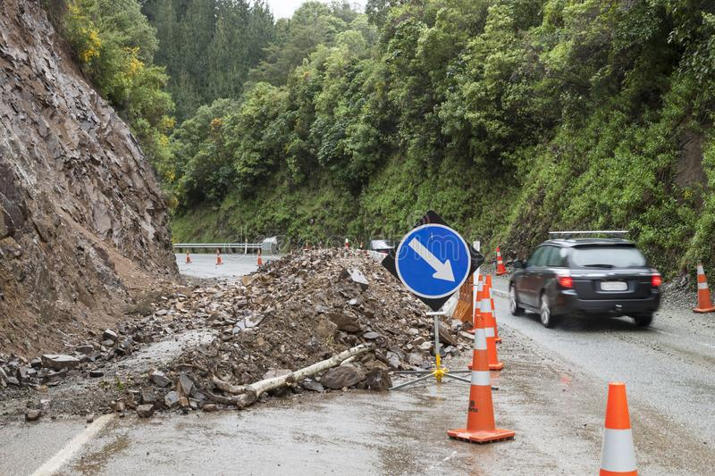 Automobile car driving past rockflall, rocks, landslide debris, traffic cones and warning signs on roadway highway. Dangerous road. Conditions hazards royalty free stock photo