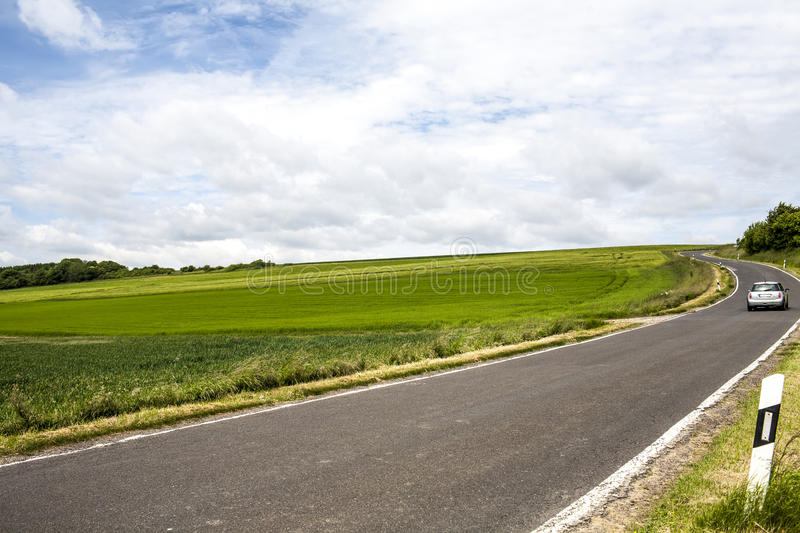 A car is driving on the national road in the countryside of Germany. Sunny weather with blue sky and white clouds, green wheat fields are on the left side of stock photography