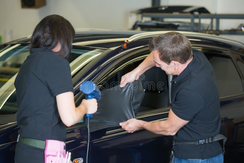 Automobile che avvolge gli specialisti che avvolgono specchio laterale con la stagnola del carbonio immagini stock