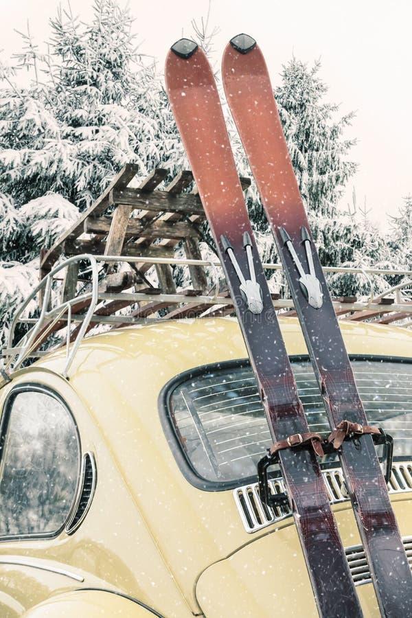 Automobile classica con lo sci d'annata e la slitta durante le precipitazioni nevose immagini stock