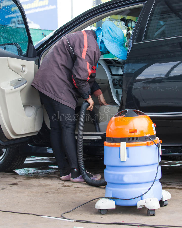 Automobile cleaning theme. Mechanic hoovering the car cabin with royalty free stock photo