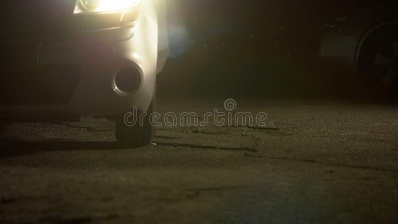 Automobile con i fari di giro che stanno sul parcheggio vuoto, atmosfera spaventosa fotografia stock