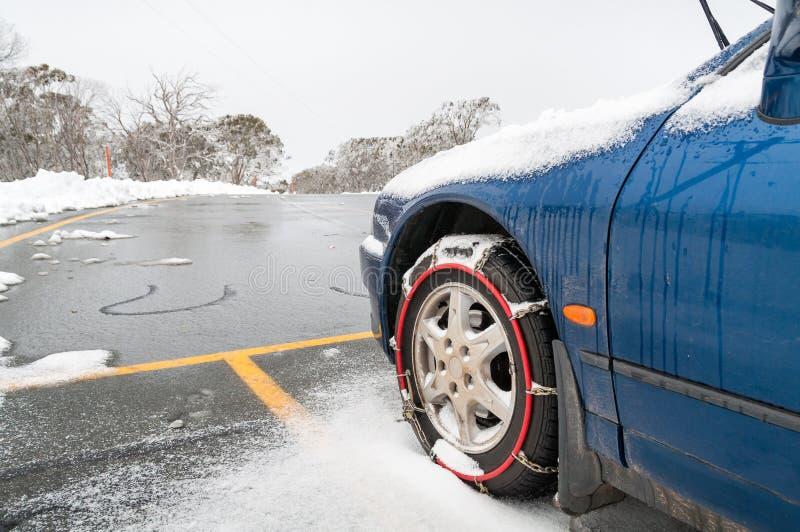 Automobile con le catene da neve o le catene di neve misura sulle sue ruote anteriori fotografia stock