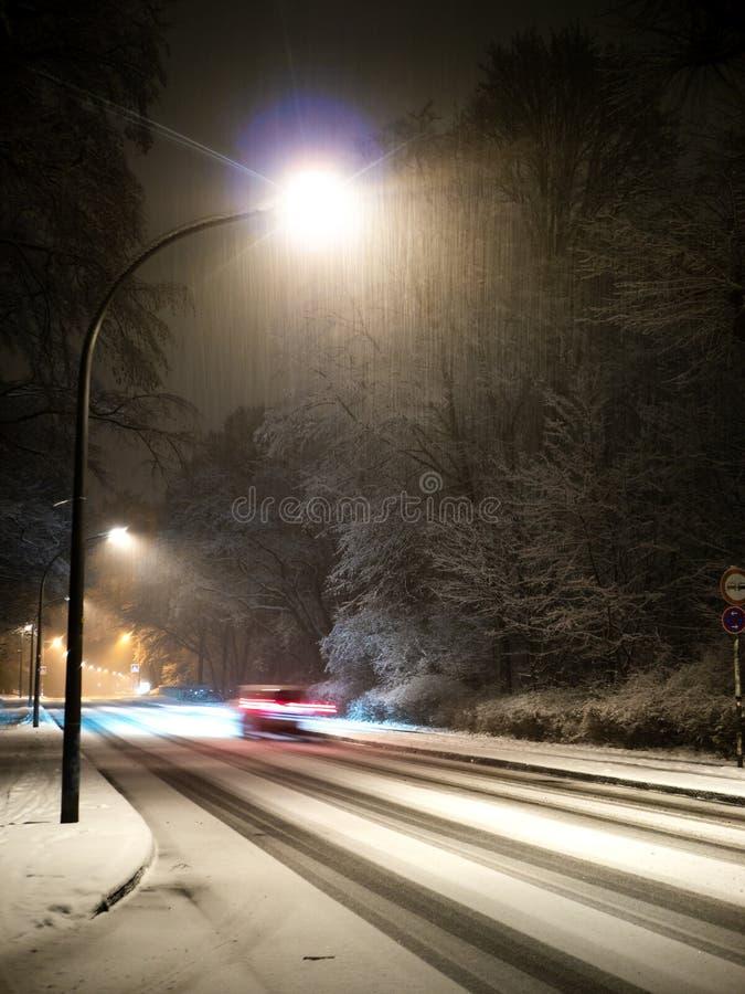 Automobile con mosso che guida su una via nevosa con le iluminazioni pubbliche alla notte fotografia stock libera da diritti