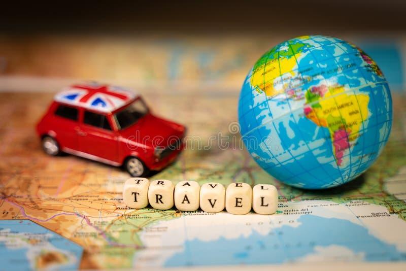 Automobile d'annata del giocattolo miniatura e un pallone della mappa di mondo su una mappa Concetto di trasporto e di viaggio fotografia stock libera da diritti