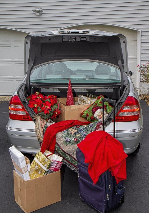 Automobile d'imballaggio con i regali di Natale, valigie pronte ad andare via per le feste immagini stock libere da diritti