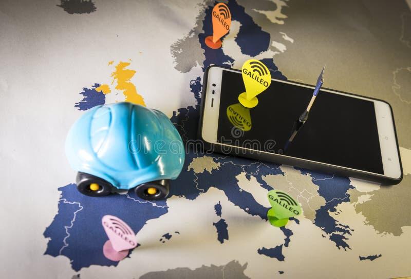 Automobile del giocattolo e uno smartphone sopra una mappa di UE Metafora del sistema di Galileo fotografia stock