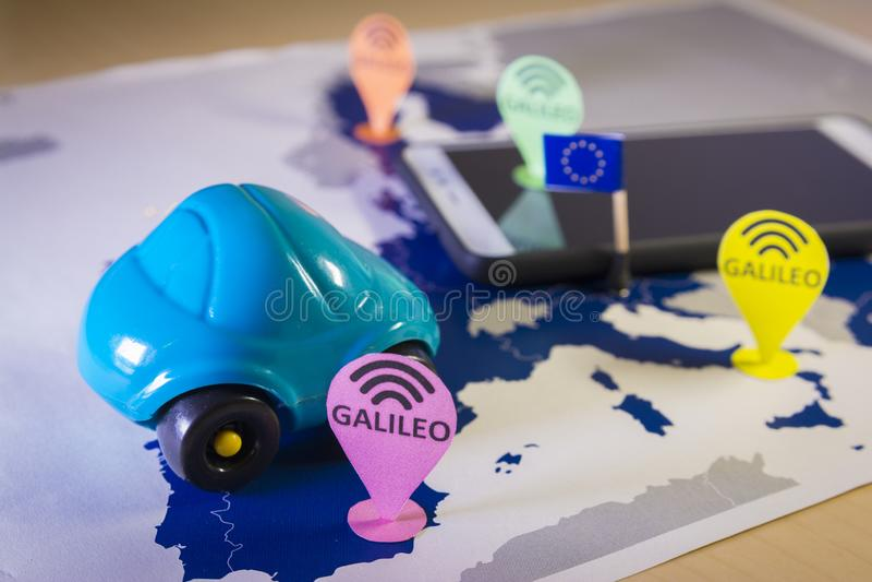 Automobile del giocattolo e uno smartphone sopra una mappa di UE Metafora del sistema di Galileo fotografie stock