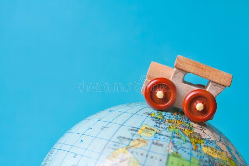 Automobile di legno del giocattolo su un globo su fondo azzurrato fotografia stock libera da diritti