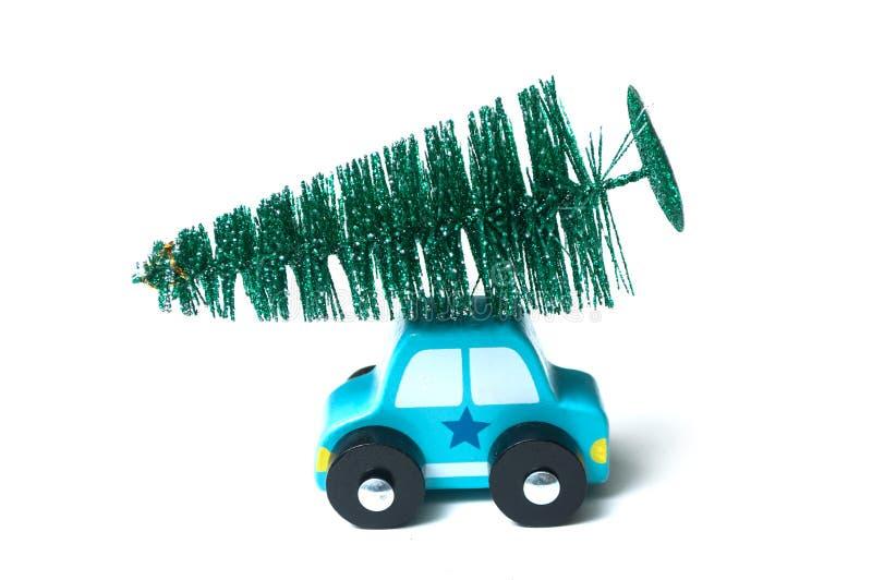 automobile di legno miniatura con l'albero di Natale sul tetto su fondo bianco fotografia stock