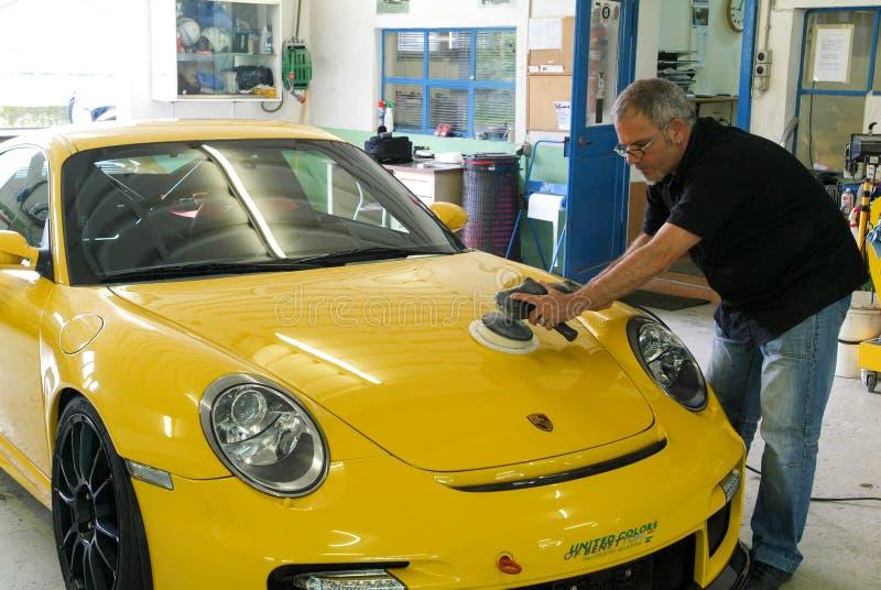 Automobile di lucidatura del meccanico nell'officina riparazioni automatica fotografia stock libera da diritti