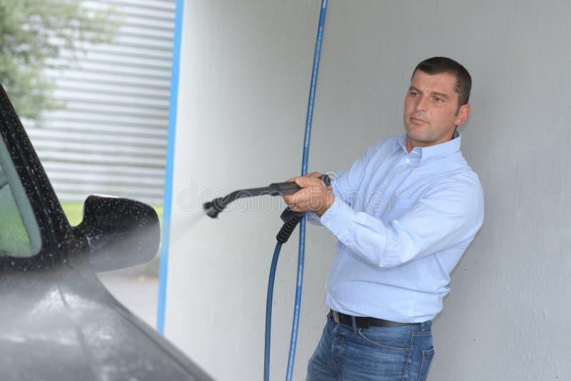 Automobile di pulizia dell'uomo con il tubo flessibile immagine stock libera da diritti