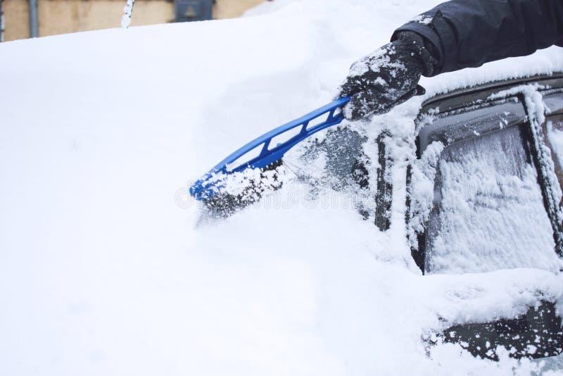 Automobile di pulizia dell'uomo da neve e ghiaccio con lo strumento della ruspa spianatrice e della spazzola durante le precipita fotografia stock