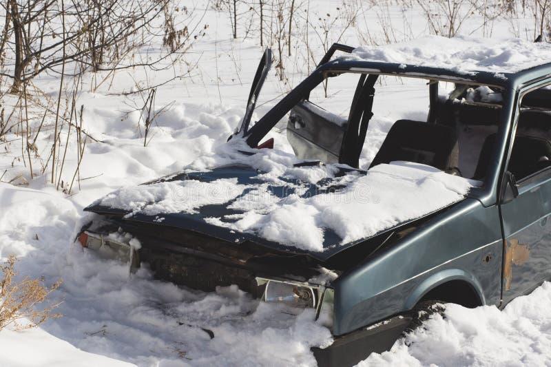 Automobile distrutta abbandonata nella neve Scheletro del tra inutile immagini stock libere da diritti