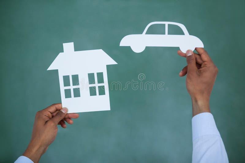 Automobile e casa del taglio della carta della tenuta dell'uomo fotografie stock libere da diritti