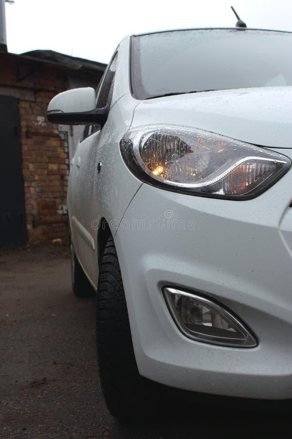 Automobile elegante bianca all'aperto con le gocce di pioggia Nuova automobile moderna fotografia stock libera da diritti
