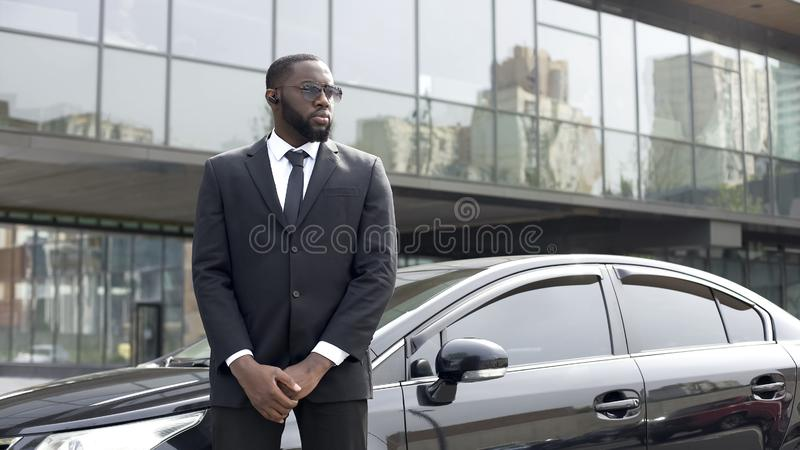 Automobile facente una pausa dell'autista afroamericano sicuro, servizio della guardia giurata, affare fotografie stock libere da diritti
