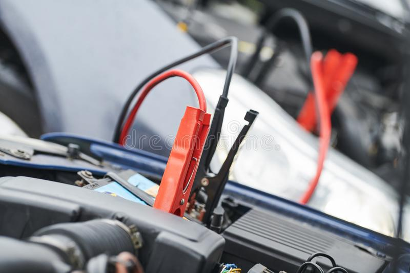 Automobile help. booster jumper cables charging automobile discharged battery. Automobile road assistance or help. engine starting problem. Car battery royalty free stock photos