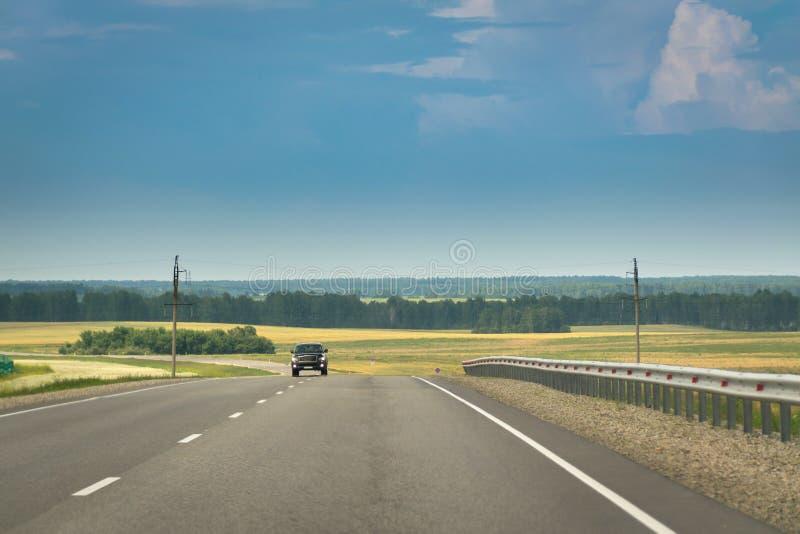 Automobile imminente su una strada principale in campagna Cielo nuvoloso e tempestoso fotografie stock libere da diritti
