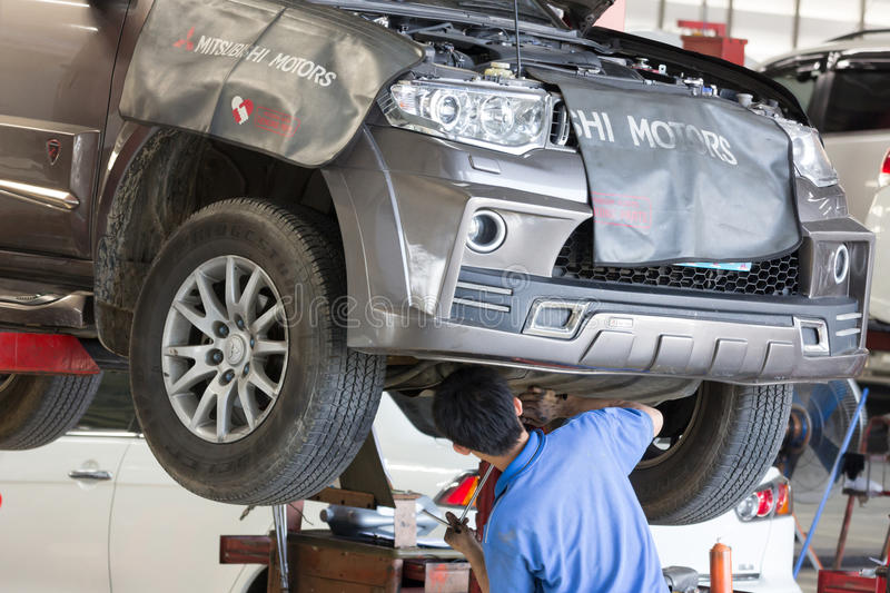 Automobile mechanic examining car suspension of lifted automobile royalty free stock photos