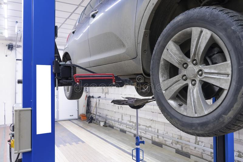 Automobile nera in garage con attrezzatura speciale per la riparazione immagine stock libera da diritti