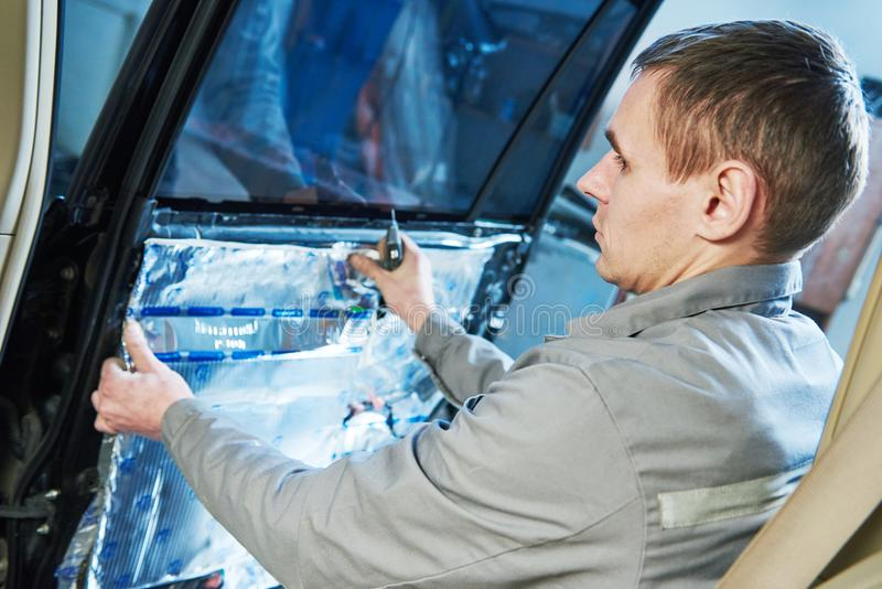Automobile noise protection and vibration reduction. Automobile soundproof, noise protection and vibration insulation. mechnic worker placing the sound damping stock photography
