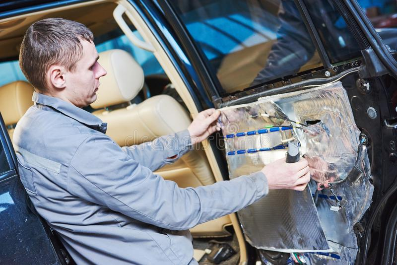 Automobile noise protection and vibration reduction. Automobile soundproof, noise protection and vibration insulation. mechnic worker placing the sound damping royalty free stock image