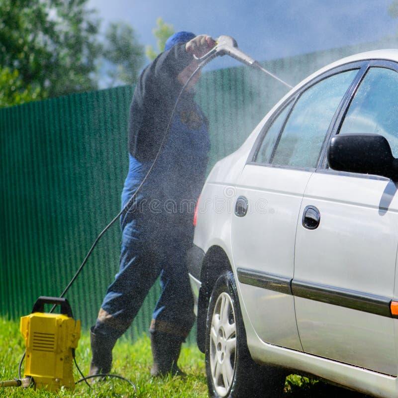 Automobile non identificata di lavaggio del lavoratore dell'uomo sotto il ou ad alta pressione dell'acqua fotografia stock