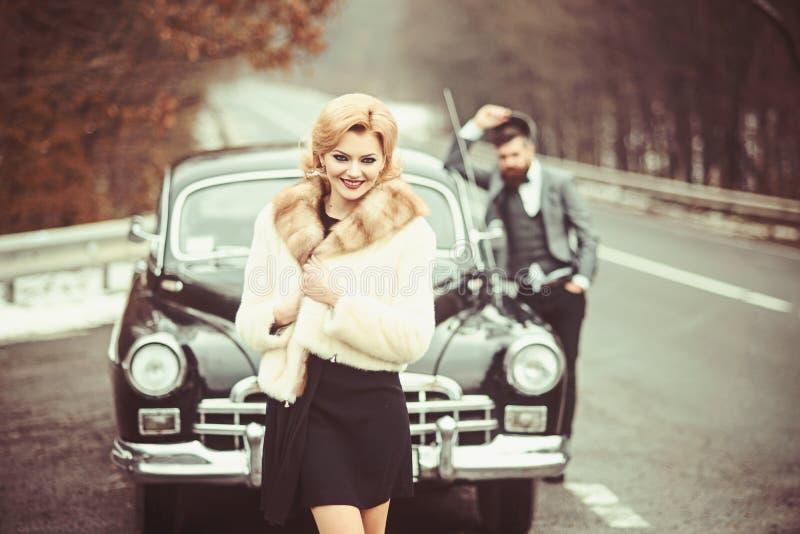 Automobile retro della raccolta e riparazione automatica dall'autista del meccanico Uomo barbuto e donna sexy in pelliccia Coppie fotografie stock