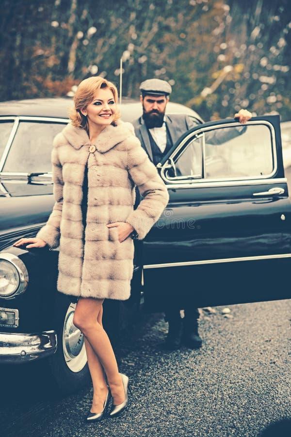 Automobile retro della raccolta e riparazione automatica dall'autista del meccanico Uomo barbuto e donna sexy in pelliccia Scorta fotografie stock libere da diritti