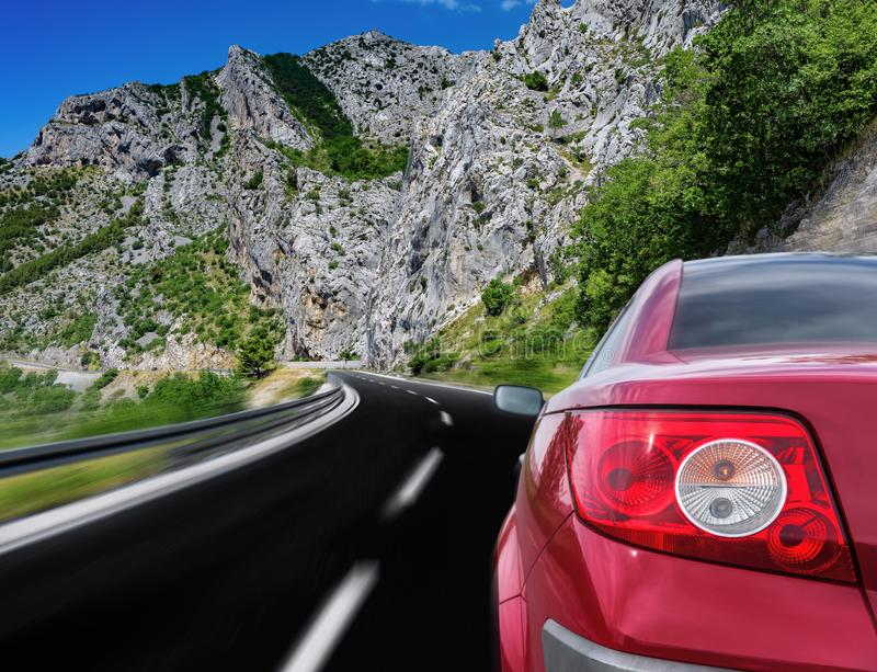 Automobile rossa che precipita lungo una strada principale ad alta velocit? fotografia stock