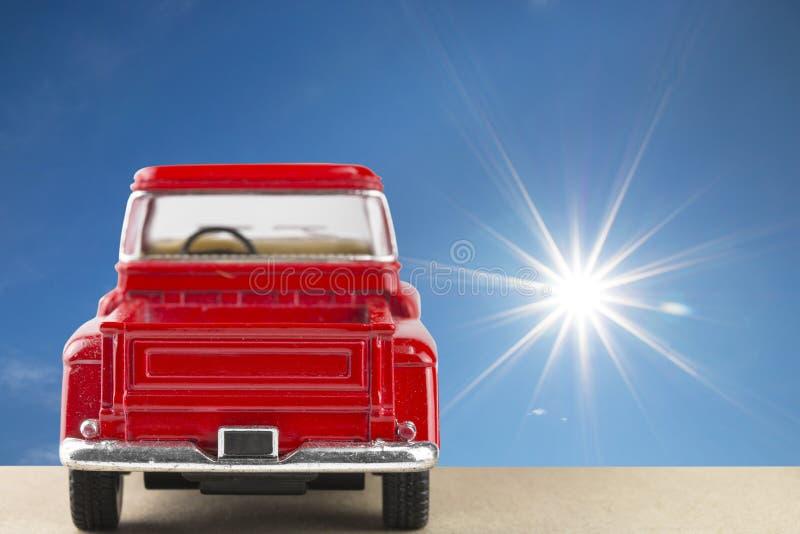 Automobile rossa con il sole brillante a chiaro cielo blu fotografie stock