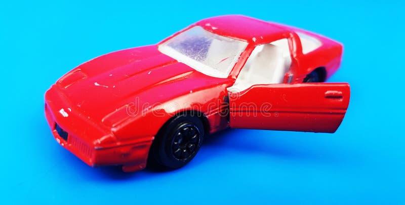 Automobile rossa su fondo blu con la porta aperta Modello dell'automobile del giocattolo fotografia stock