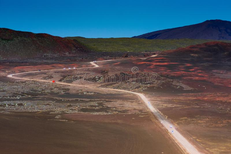 Automobile rossa sulla strada nel paesaggio asciutto che conduce al vulcano di Reunion Island fotografia stock