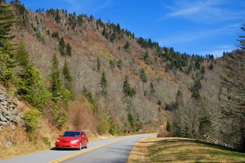 Automobile rossa sulla strada principale fotografia stock