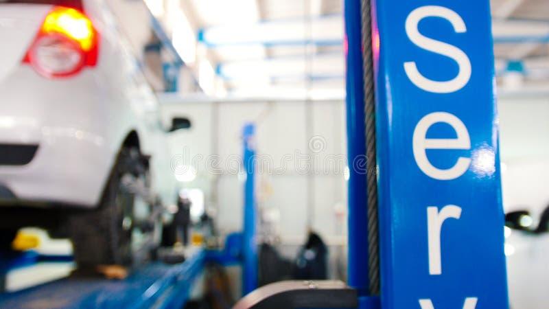 Automobile sollevata in servizio il servizio professionale - il crollo di convergenza - riparazione trattata, fondo defocused fotografia stock