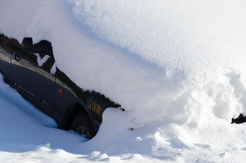 Automobile sotto il cumulo di neve nell'iarda della città dopo le precipitazioni nevose pesanti immagini stock
