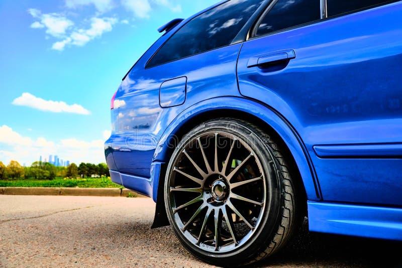 Automobile sportiva aggressiva in blu contro lo sfondo della natura immagine stock