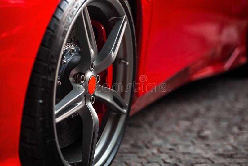 Automobile sportiva rossa con il dettaglio sulla gomma brillante della ruota fotografia stock libera da diritti