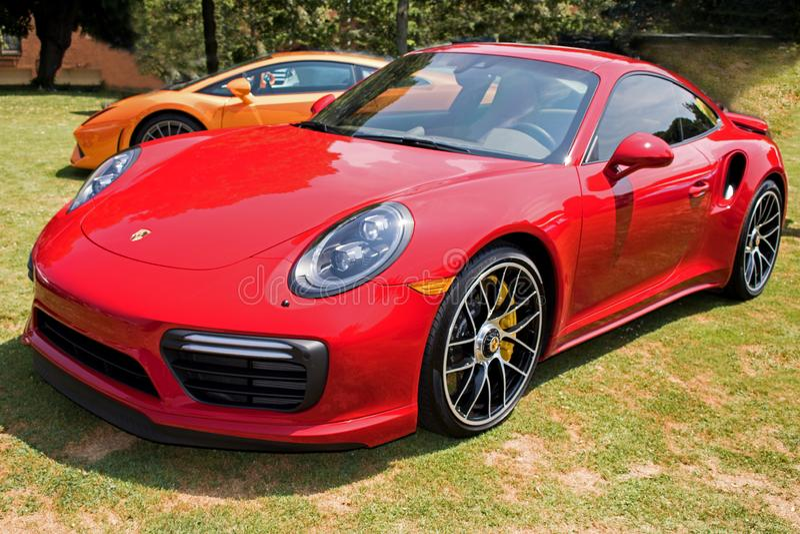Automobile sportiva rossa di Porsche nel campo di erba fotografia stock libera da diritti