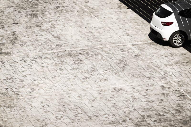 Automobile su un parcheggio con il pavimento piastrellato grigio fotografie stock libere da diritti