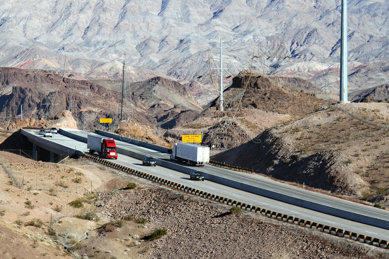 Automobiles running on highway through mountains. Nevada stock photography