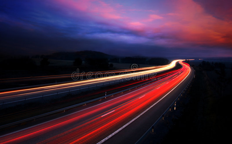 Automobili alla notte con la sfuocatura di movimento immagini stock